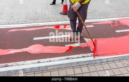 Workman repainting city cycle path. - Stock Image
