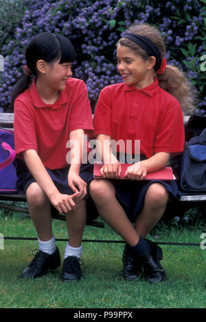 two schoolgirls sitting on bench chatting - Stock Image