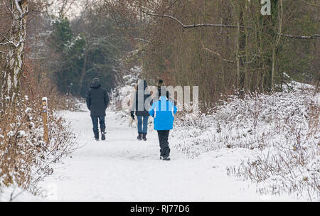 Snow landscape, wit people walking through pathway around Frogmore Lakes, St. Albans, UK - Stock Image