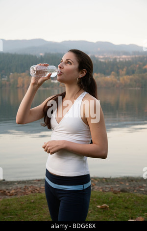 A young athletic woman drinking from a plastic water bottle next to a lake. - Stock Image