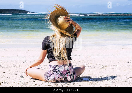 Beautiful blonde young caucasian woman tourist at the beach on vacation enjoying the sand and feeling the freedom - blue sea and sky in background - t - Stock Image