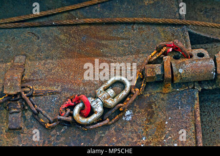 Rusting chains and well-worn swivels attached to a trawler's otter board in Scarborough Harbour. - Stock Image