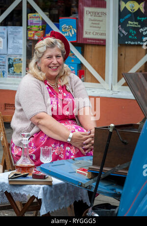 Woodhall Spa 1940s Festival - woman dressed in 1940s outfit sat at the street party - Stock Image