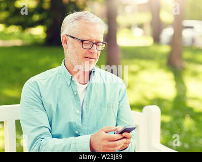 happy senior man texting on smartphone at summer - Stock Image