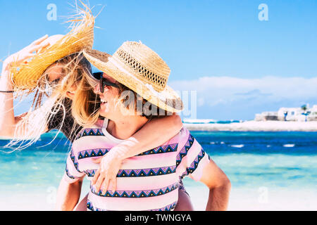 Happy and cheerful young people couple laughing and having fun in outdoor leisure activity at the beach during summer holiday vacation together - happ - Stock Image