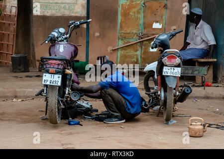 A man repairs a motorcycle in Burkina Faso, west Africa. - Stock Image