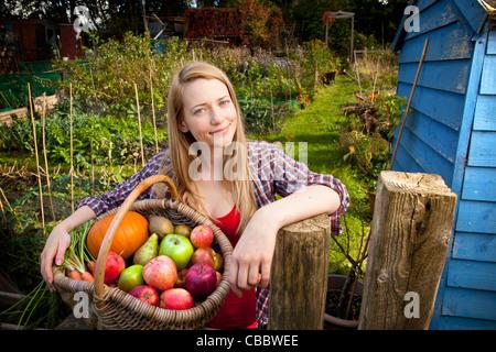 Woman gathering vegetables in garden - Stock Image