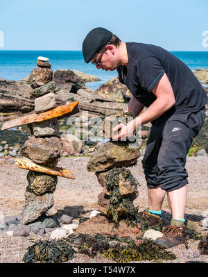 Dunbar, East Lothian, Scotland, UK. 21st Apr 2019. European stone stacking championship: Dennis Jablonski  balances stones in the  artistic competition, giving competitors 3 hours to create anything from stones or found objects competition at Eye Cave beach on the second day which comprises 2 competitions, a 3 hour artistic challenge and a children's competition. The overall winner receives a trip to llano Earth Art Festival & World Stone Balancing competition in Texas in 2020. Credit: Sally Anderson/Alamy Live News - Stock Image