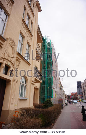 Poznan, Poland - March 8, 2019: Building under construction by a sidewalk on the Slowackiego street in the city center on a cloudy day. - Stock Image