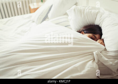 Tired young woman sleeping in bed - Stock Image