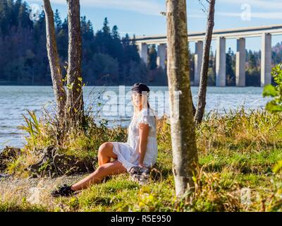 Adolescent teenager girl pretty natural in nature sitting near lake dressed in short White robe dress - Stock Image
