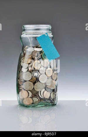 Glass Savings Jar with Pound Coins - Stock Image