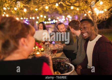 Friends talking, enjoying dinner garden party - Stock Image