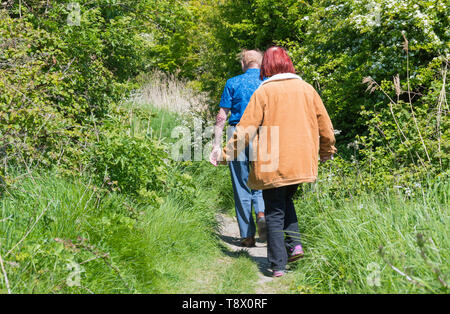 Senior couple of people walking along a country footpath in Spring in West Sussex, England, UK. - Stock Image