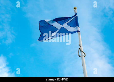 Looking up at saltire Scottish national flag or St Andrews cross, with blue sky background, Scotland, UK - Stock Image
