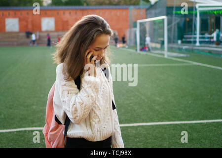 Young girl in a white sweater tries to call. High school student holding a mobile device. Phone call on school grounds. Soccer field in background - Stock Image
