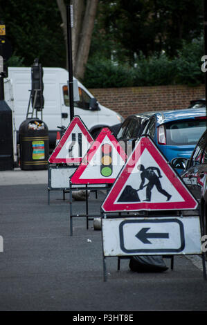 Men at work, traffic light and road narrows contruction signs in stoke newington, hackney, london - Stock Image