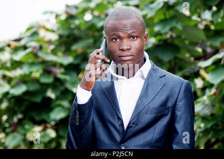 portrait of african businessman standing and communicate with his mobile phone. - Stock Image