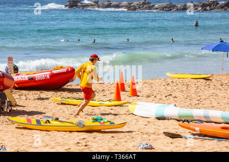 Surf rescue volunteer with surf rescue dinghy and surfboards on Palm Beach, Sydney,Australia - Stock Image