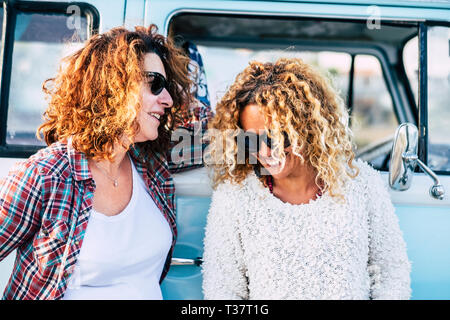 Happy people outdoor - couple of curly cute middle age adult women friends enjoy together the trip with old vintage blue van in background - laudh and - Stock Image