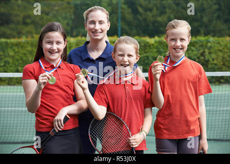 Portrait Of Winning Female School Tennis Team With Medals - Stock Image