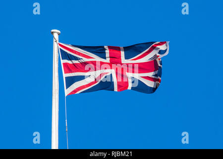 A view of a Union flag flying over a clear blue sky. - Stock Image