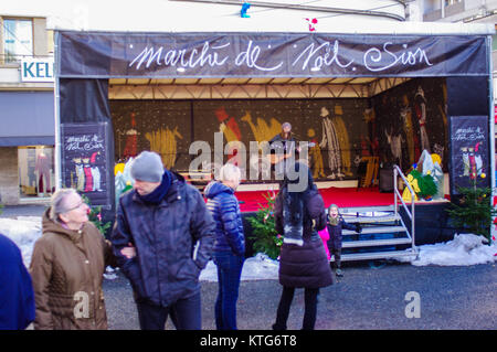 People out for the Marche de Noel Sion where they are Chistmas shopping.  Band playing in concert. - Stock Image