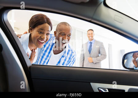 happy African couple choosing luxury car at vehicle dealership looking at the interior - Stock Image