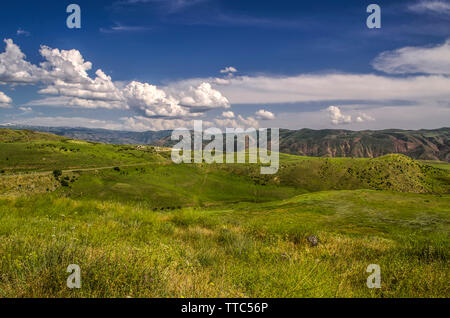 View of the highway with a turn leading to the Garni temple among the mountains of Geghama ridge in Armenia against the blue sky covered with huge clo - Stock Image