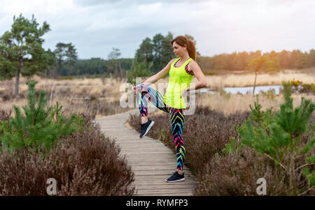 woman doing exercises in the morning sun, leg stretch. - Stock Image
