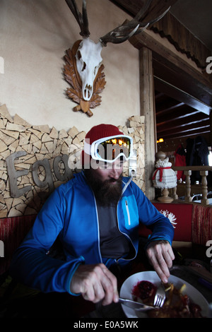 Mid adult male skier enjoying restaurant meal, Tyrol, Austria - Stock Image