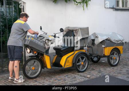 Postman (mailman) at work in Basel, Switzerland - Stock Image