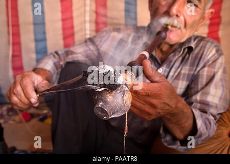 Qashqai man smoking tobacco with traditional pipe,  nomad people, Iran - Stock Image
