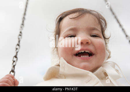 Happy 2 year old girl having fun on a swing on winter. Selective focus - Stock Image