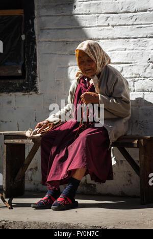 Elderly woman wearing crimson robe and holding Buddhist prayer beads sitting on wooden bench in Trongsa, Bhutan - Stock Image