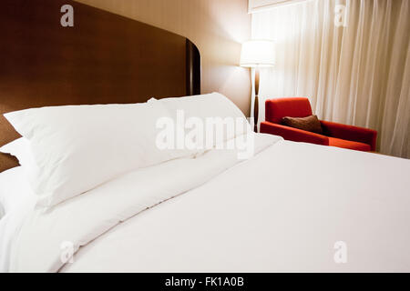 Modern hotel room with a bed, lamp and red chair - Stock Image
