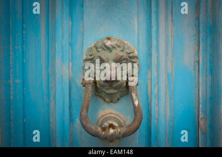 A rusty brass knocker on a weathered blue door in a coastal town in Malta - Stock Image