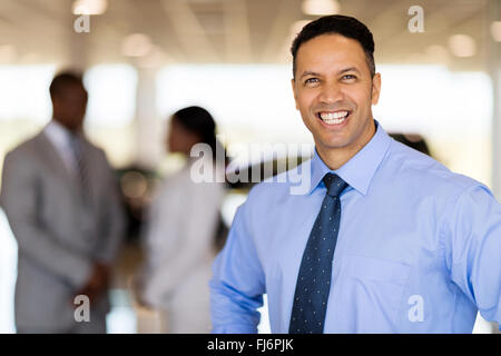 happy middle aged male vehicle sales consultant in showroom - Stock Image