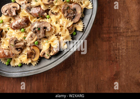 Mushroom and cheese pasta. Farfalle with cremini and green peas, top shot on a dark rustic wooden background with copy space - Stock Image