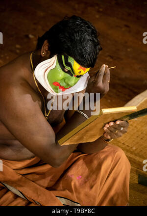 Vertical aerial view of the lead Kathakali performer putting on the distinctive green make up in Kerala, India. - Stock Image