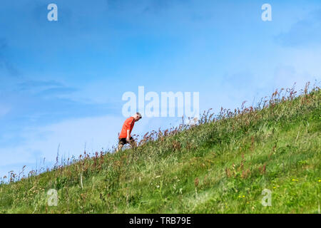 A man wearing a bright red top seen against a blue sky walking up a steep grass covered slope in the countryside. - Stock Image