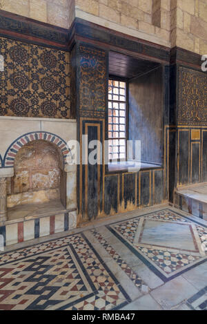 Wooden wall decorated with painted floral patterns, embedded arched niche and marble floor decorated with geometric patterns at ottoman era house - Stock Image