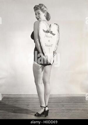 Bathing beauty holding heart-shaped sign - Stock Image