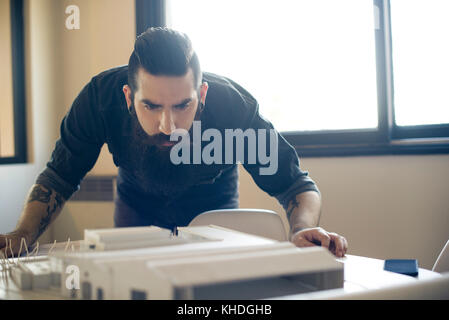 Architect looking at model building - Stock Image