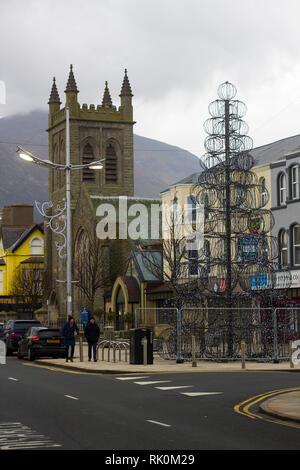 14 December 2018 The contemporary design Christmas tree in newcastle County Down with Newcasle Presbyterian Church and the Slieve Donard mountain peak - Stock Image