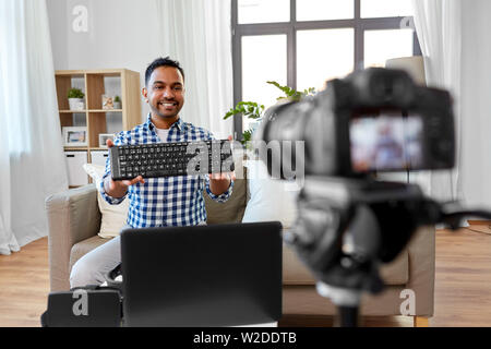 male blogger with keyboard videoblogging at home - Stock Image