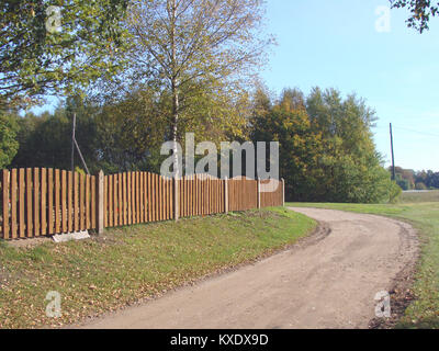 Brown color paint fence from wooden laths and concrete poles - Stock Image