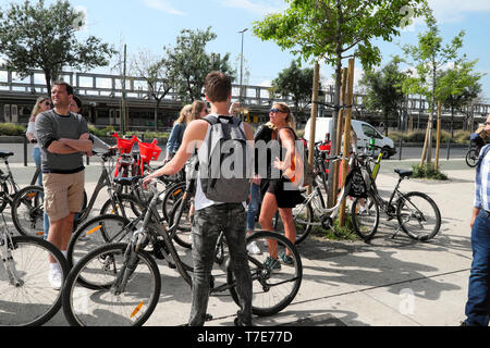 Young people with bike hire bikes and tour guide outside Time Out food Market building entrance Ribeira Lisbon Lisboa Portugal Europe EU  KATHY DEWITT - Stock Image
