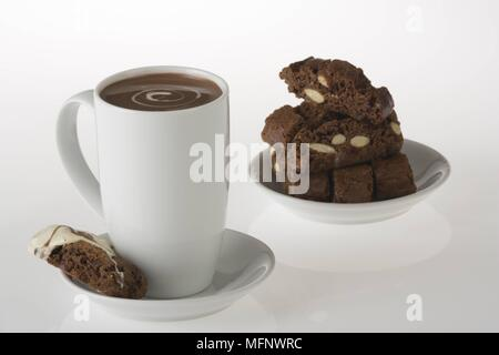 White porcelain cup with drinking chocolate. Almond and chocolate biscoti in background. Studio shot.      Ref: CRB538_103609_0016  COMPULSORY CREDIT: - Stock Image