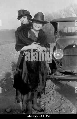 Two women hug while posing with their automobile along a Colorado road, ca. 1920. - Stock Image